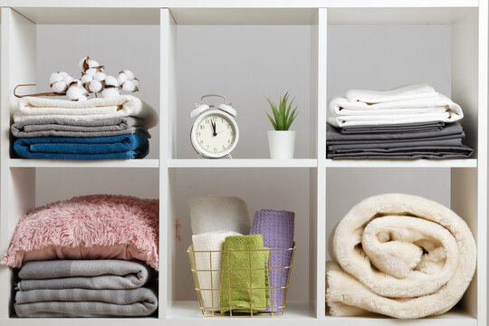 Organization of storage. Stacks of towels, sheets, bed linen, blankets and pillows on a white shelf.