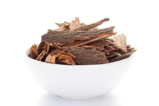 close-up of Organic cinnamon ( Cinnamomum verum) or dalchini on a ceramic white bowl. Pile of Indian Aromatic Spice.