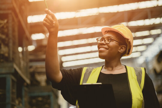 Black African professional women worker happy working count checking inventory production stock control in business factory  industry warehouse waring engineer suit and helmet for safety