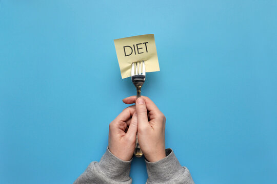 The word diet is on the fork. A person on a diet, the desire to lose weight