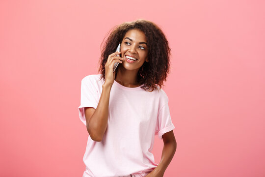 Girl calling friend to meet up. Portrait of charming friendly and outgoing african american young woman with afro hairstyle holding smartphone near ear while talking looking left curiously