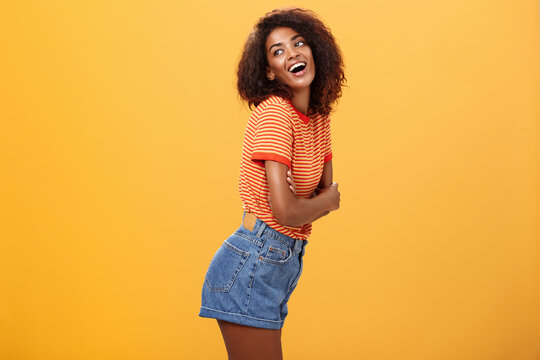 Hey wanna hang out. Sensual and flirty carefree stylish dark-skinned woman with curly hair standing in profile turning left and posing with happy cute expression smiling and seducing over orange wall