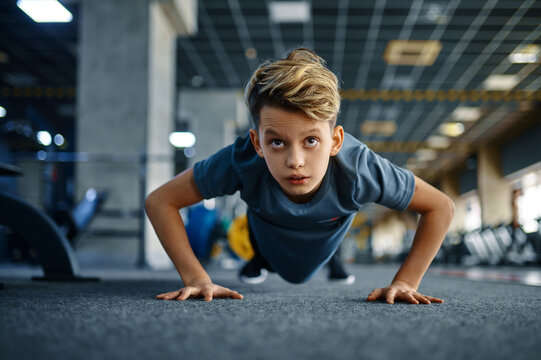 Boy doing push up exercise in gym, front view