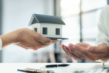 Fototapeta Property investment concept, image of small house model on the table. and home loan insurance.