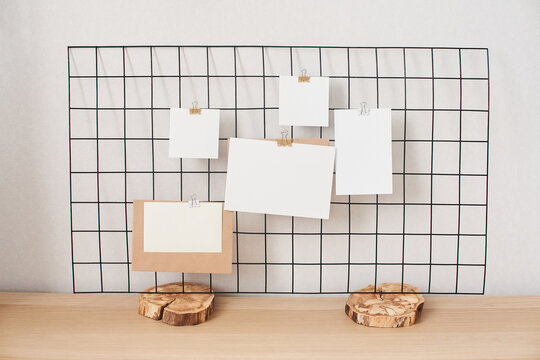 Cards and posters mock ups on black grid board on wooden stand. Blank paper in different sizes attached with binder. Template for prints, photography, to do or planning lists.