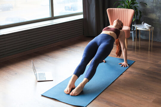 Sporty slim woman practicing advanced yoga in front of laptop, watching online tutorials. Healthy lifestyle.