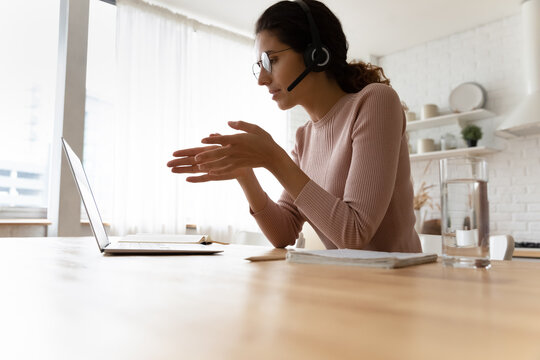 Low angle view of hispanic female wear glasses headset take part in virtual event talk by video call on pc. Young woman remote employee discuss business affairs negotiating online in conference mode
