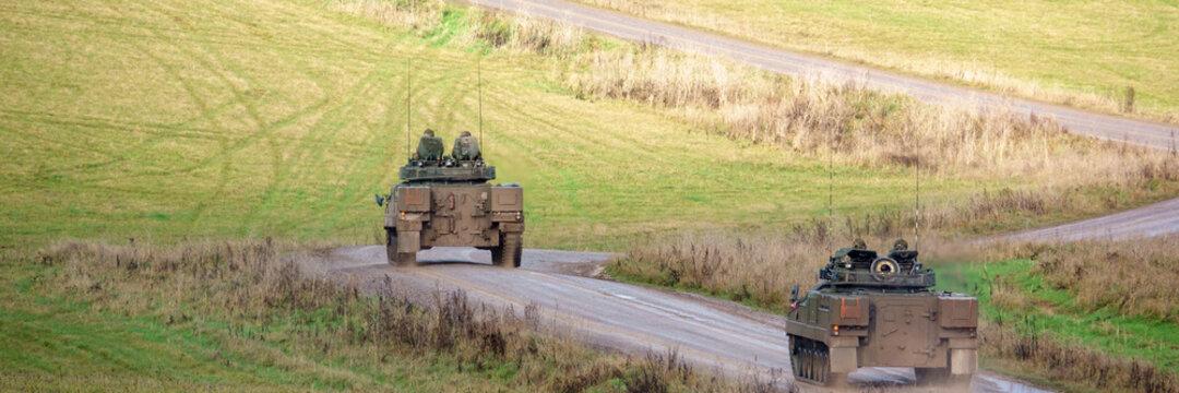 panorama of British Army Warrior FV510 Light Infantry Fighting Vehicle combat tanks on maneuvers Salisbury Plain military training grounds, Wiltshire