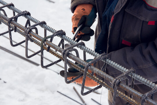 Concrete reinforcement. Tool at a construction site. The construction tool for monolithic works. Workers hands using steel wire and pincers to secure rebar
