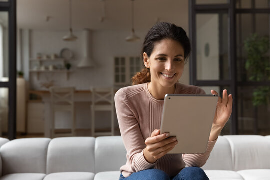 Confident millennial latin woman hold tablet zoom in image photo picture on screen enjoy good work of new web app. Positive young female scroll text on pad read pleasant message email electronic book