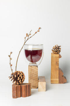 Still life with a refreshing drink with extracts of natural herbs, eleutherococcus, licorice, eucalyptus and essential oils of coniferous trees, in a glass, with wooden stands and cones. Vertical