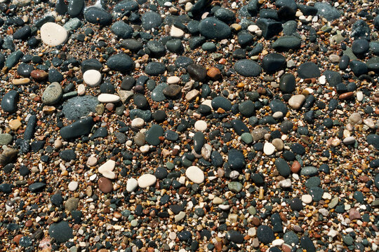 wet multi colored stones and pebbles on sea beach
