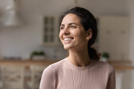 I am doing fine. Smiling motivated young latin lady look at distance with belief in good hope visualize optimistic future. Cheerful millennial female enjoy beautiful day feel happy at home. Copy space