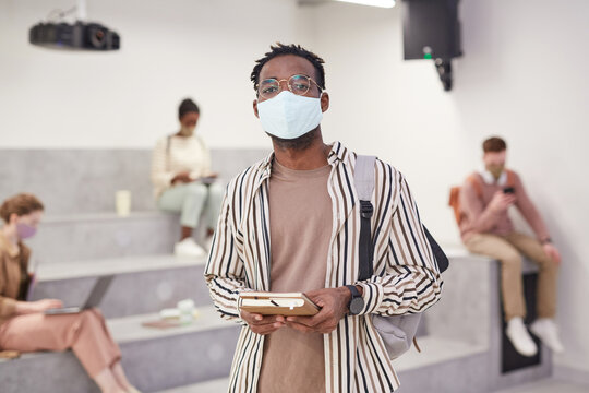 Waist up portrait of adult African-American student wearing mask and looking at camera while standing in modern school lounge, copy space
