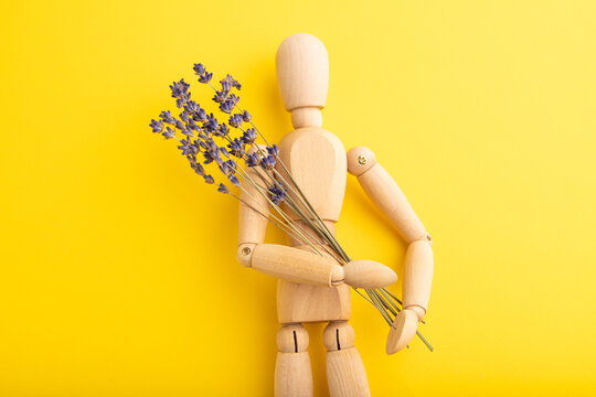 Wooden mannequin holding lavender flowers on yellow pastel background. copy space.