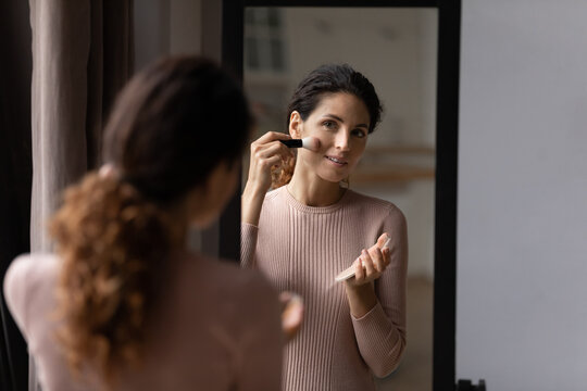 Morning make up. Charming latin female look at mirror hold powder compact container put flour on face with big brush. Happy young woman enjoy visage use professional color cosmetic pressed dry blusher