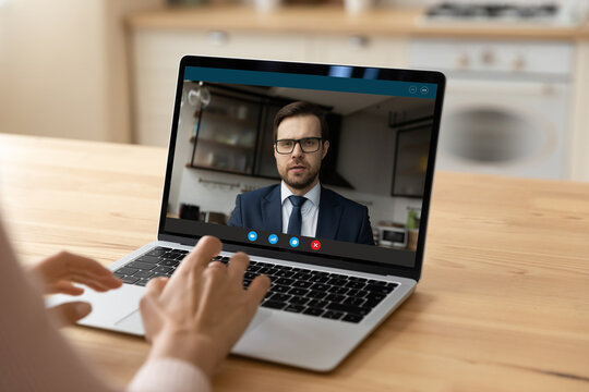 Confident young businessman in glasses on pc screen consult support female client by video call. Millennial male manager working from home office has remote meeting with customer using conference app