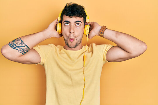 Young hispanic man listening to music using headphones making fish face with mouth and squinting eyes, crazy and comical.