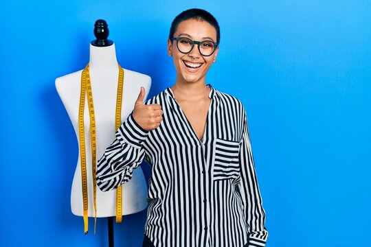 Beautiful hispanic woman with short hair standing by manikin smiling happy and positive, thumb up doing excellent and approval sign