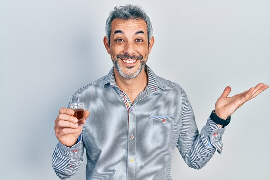 Handsome middle age man with grey hair drinking whiskey shot celebrating victory with happy smile and winner expression with raised hands