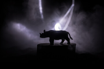 Fototapeta Rhino miniature standing at foggy night. Creative table decoration with colorful backlight with fog