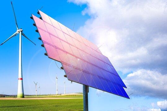 Solar panels and wind generators under blue sky