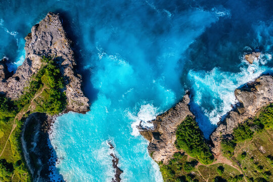 Waves and rocks as a background from top view. Blue water background from top view. Summer seascape from air. Bali island, Indonesia.