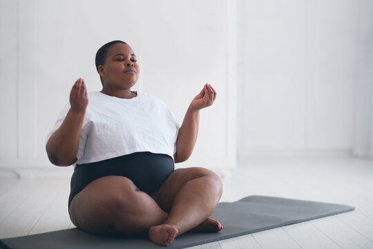 beautiful plus size woman doing yoga exercise at home