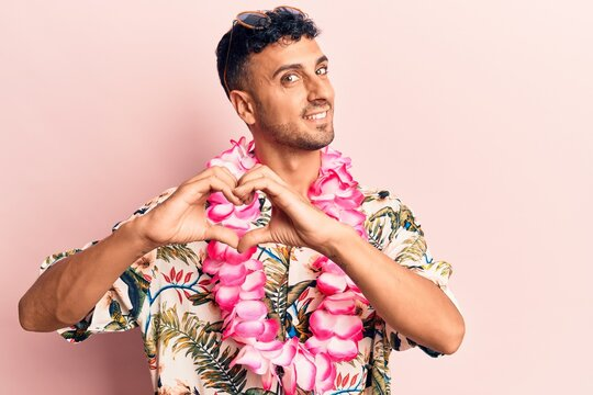 Young hispanic man wearing summer casual clothes smiling in love doing heart symbol shape with hands. romantic concept.