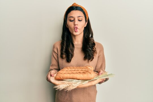 Young hispanic woman holding bread making fish face with mouth and squinting eyes, crazy and comical.