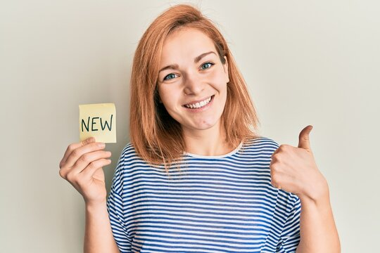 Young caucasian woman holding reminder with new word smiling happy and positive, thumb up doing excellent and approval sign