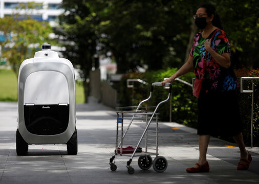 A woman pushes a trolley past Camello, an autonomous grocery delivery robot, in Singapore