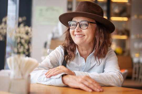 Beautiful mature senior woman in glasses and a hat sitting in a cafe and smiling looking at the camera