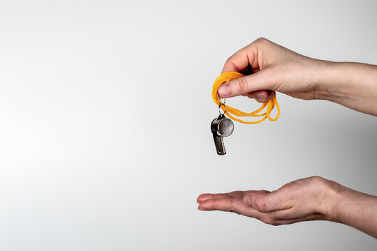 Woman's hands with a whistle on a white background. Copy space