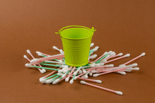 Small bucket and cotton swabs on a brown background.