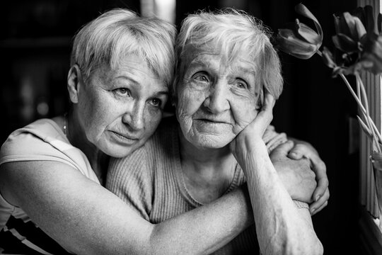 An old woman with her adult daughter. Black and white photo.