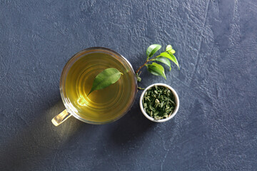 Printed kitchen splashbacks Asia Country Cup of green tea and dry leaves on dark background