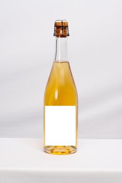 Full champagne wine bottle mock up with blank label on white table background