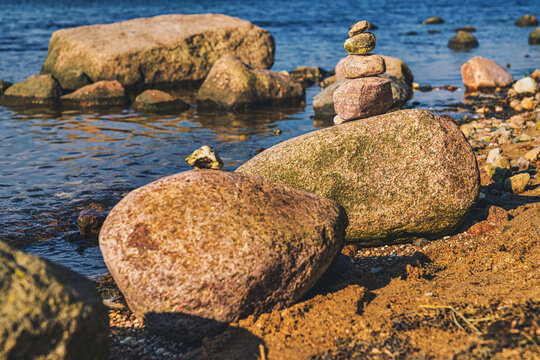 Cairns on a beach with water in the background