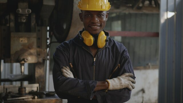 Portrait American industrial black young worker man smiling with yellow helmet in front of machine, Happy engineer standing arms crossed at work in the industry factory, manufacturing.