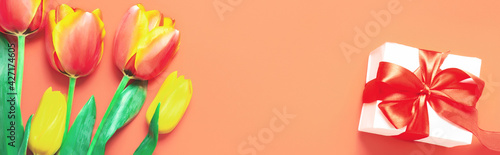 Spring flowers banner - bunch of colorful tulips flowers on orange background. Easter day, Mother day mock up greeting card. Congratulation or Invitation card with free space for text.
