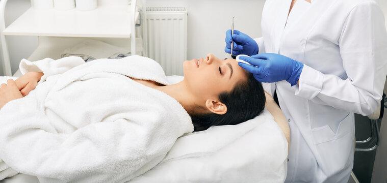 Cleansing face. Brunette woman with eyes closed while mechanical cleansing facial skin from defect and remove blackhead