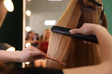 Stylist straightening woman's hair with flat iron in salon