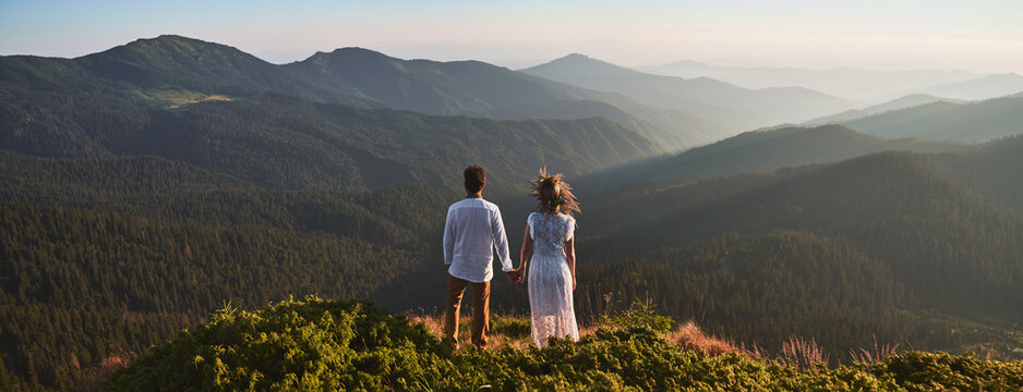 Back view of loving couple standing on grassy hill and holding hands while looking at beautiful mountains. Young man holding hand of charming woman in white dress and admiring beauty of nature.