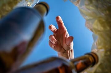 Hand sammelt Pfandflaschen aus einem Mülleimer ein