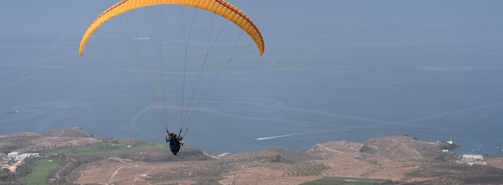 Paraglider tandem flying over the ocean with blue water in bright sunny day