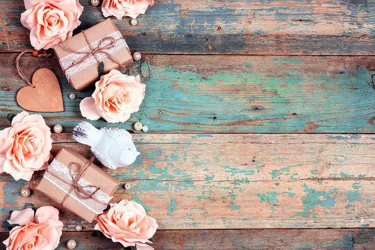 Festive background with rose flowers, gifts and bird on shabby wooden turquoise boards. Border top down composition with copy space.