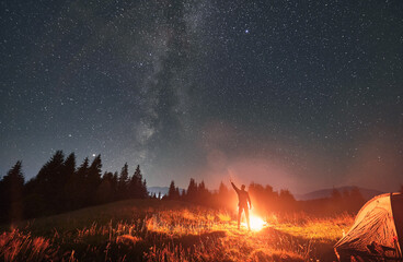 Fototapeta Silhouette of man hiker near campfire, pointing finger at beautiful night starry sky with Milky Way under mountain valley with tourist tent. Concept of hiking, travelling and night camping.
