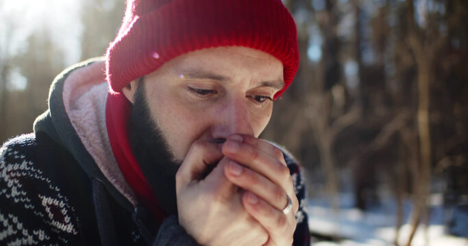 Young man hiker got lost in winter forest and blowing at frozen hands trying to get warm