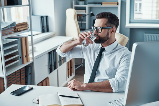 Good looking young man in shirt and tie drinking water while sitting in the office